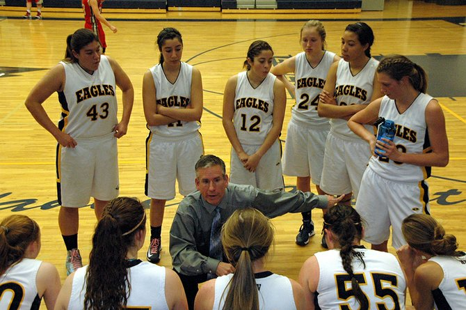 TIME TO REGROUP for the HRVHS varsity girls basketball team and coach Scott Walker during Satur-day's contest against the South Albany Rebels.