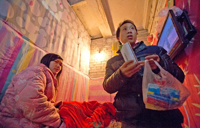 Wu Yongyuan, right, shows medicines his wife Gong Qifeng, left, takes to control her schizophrenia symptoms in a room they rent in Beijing as Wu keeps petitioning to China's central government for help on Jan. 4.