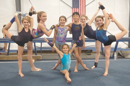 RIVERSIDE GYMNASTS (pictured from left to right) Krissy Carter, Alexa Baldy, Halle Haskins, Poppy Miller, Meara Crawford, Emily Adams and Jacy Johnson (doing the splits), all scored first place finishes at the recent Oregon Gymnastics Championship in Grants Pass on Dec. 7.