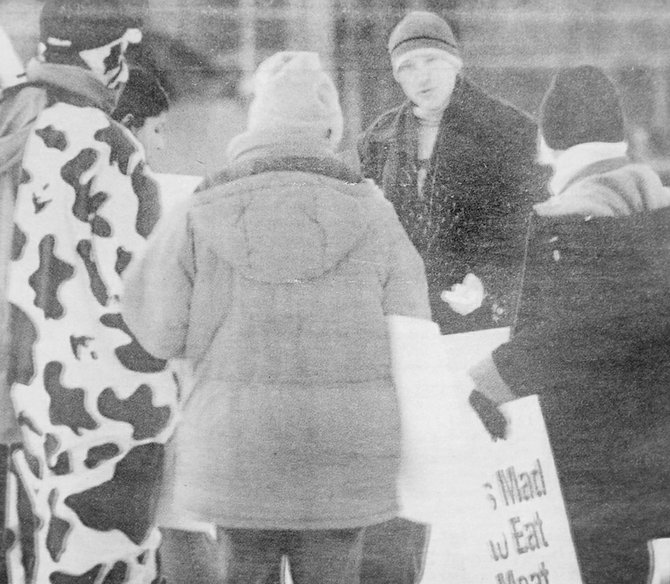 2004: Sunnyside's Greg Uberuaga (background) talked to members from the People for the Ethical Treatment of Animals (PETA) while eating a hamburger. Uberuaga was showing support for the dairy industry, while the PETA group held a demonstration in front of Sunnyside's Safeway store in reaction to Mad Cow Disease being linked to a cow from Mabton.