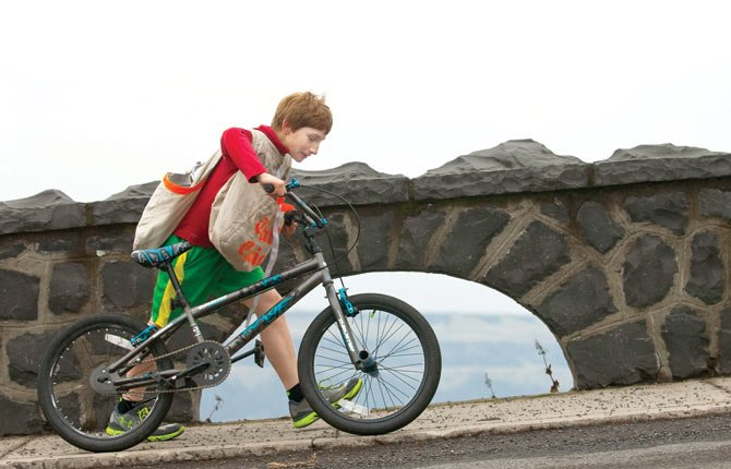Dusty Dodge trots his bike up the steepest portion of Fourth Street Grade doubletime, despite a double-route load of newspapers, as he rushes to get his routes delivered before wrestling practice Wednesday afternoon.