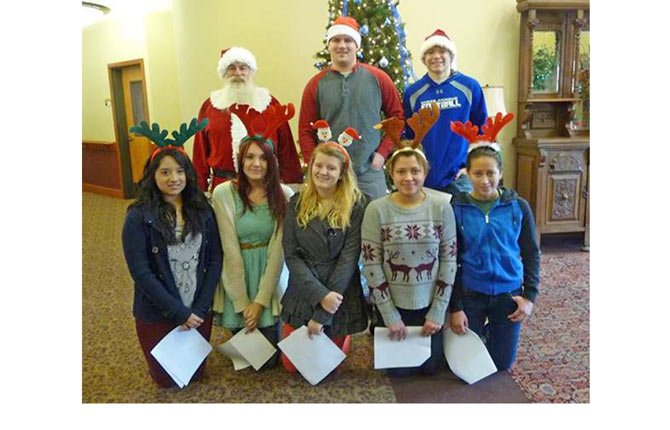 At Oregon Veterans Home YoHoH volunteers sang Christmas carols to a patient whose family joined in the singing. Pictured, back row, from left: Santa Robin Pereyda, Connor Shortt, Youth of Heart of Hospice (YoHOH) co-President Blake Diede; front row: Kimberly Mendoza, Brooklynn Tammen, co-president Hannah Lupkas, Alicia Anderson, and Shaila Anderson. Not pictured, Gail Suzuki RN and Jayne Mederios, volunteer coordinator with Heart of Hospice.	Contributed photo