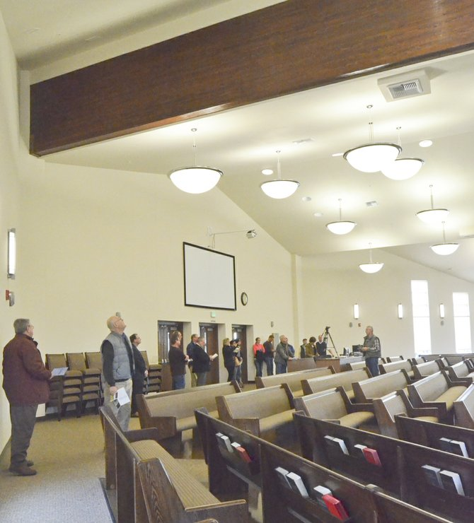 Those attending this past Monday's Sunnyside Noon Rotary Club meeting tour the facilities at Sunnyside Christian Reformed Church, which was constructed last year. While looking at the exposed 70-foot beams in the sanctuary, Leroy Werkhoven (far right) explains to Rotarians the design of the room that seats more than 500 people.