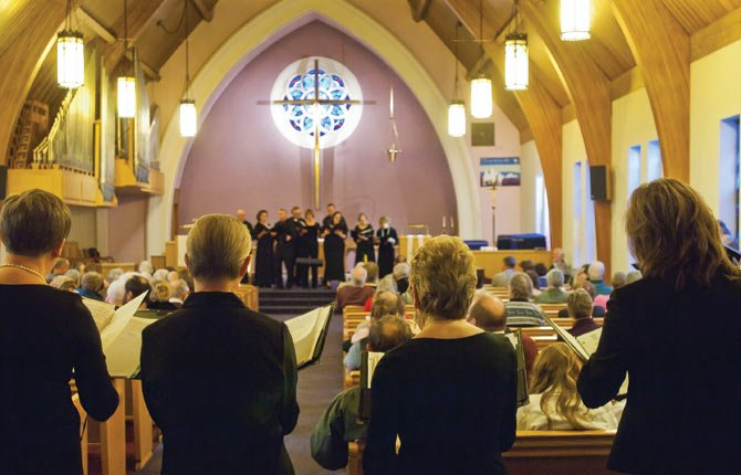 FOUR CHOIRS, arranged on four sides of the audience, perform Domine Deus, a 4-part sacred canon, during a Cascade Singers performance at Zion Luthern Church in The Dalles Jan. 12. The December performance was cancelled due to snow, and featured the Cascade Children's Choir performing holiday songs.