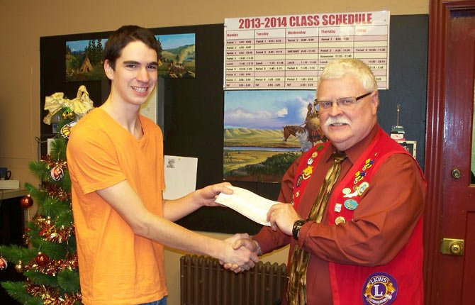 Cole McDowell, ASB president of The Dalles Wahtonka High School, presents Lion's Club Vice President Tim McGlothlin with the check for funds students raised to aid relief efforts in the Philippines.