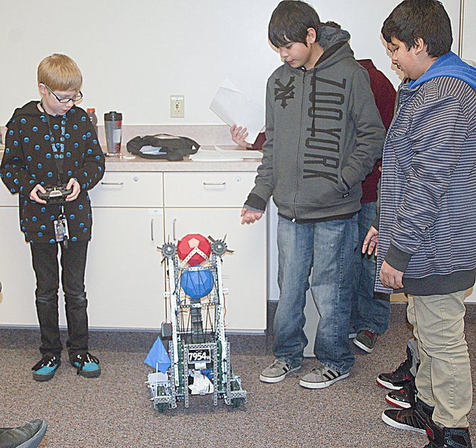 "Grand Theft Robot team members demonstrate the power of their ""Steambot"" at Wednesday morning's Sunnyside Daybreak Rotary Club meeting. The Harrison Middle School robotic engineers have competed in three contests to date and are planning a trip to Wahluke on Saturday, Jan. 18, to compete with other middle school robotic teams, according to team advisor Kari Bliesner. Pictured (L-R) are Austin Bliesner, Leo Madrigal and Nathan Guzman. Also present were Jared Salmeron and Vincent Martinez."