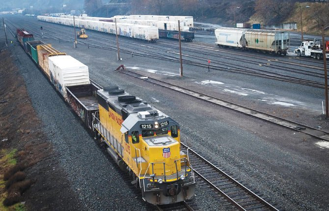 A yard engine prepares to back rail cars into a siding leading to the AmerTies plant in The Dalles, photographed from the overpass leading from downtown to Interstate 84 and Riverfront Park.