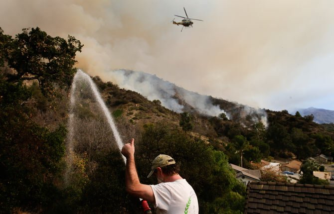 Mark Davis gives a thumbs-up toward a helicopter as he sprays water around his property, Thursday, Jan. 16, 2014, in Azusa, Calif. A wildfire burned out of control near homes in the dangerously dry foothills of the San Gabriel Mountains early Thursday, fanned by gusty Santa Ana winds that spit embers into neighborhoods in the city below, igniting trees. Evacuations were ordered for houses at the edge of the fire.