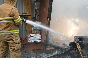A PAINT CAN explodes in the above photo while firefighters battle a tool shed fire Wednesday morning at 3910 Belmont Drive. The shed was almost totally consumed by the blaze, which West Side Fire Marshall Jim Trammell suspected was electrical in ori-gin. No one was injured.