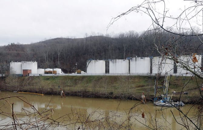 Workers inspect an area outside a retaining wall around storage tanks where a chemical leaked into the Elk River at Freedom Industries storage facility in Charleston, W.Va.