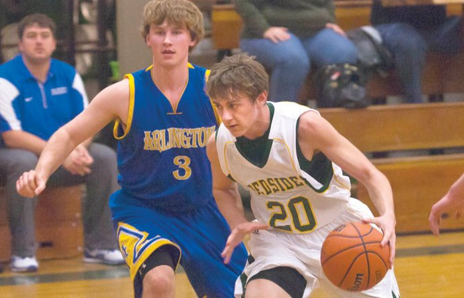 South Wasco sophomore Travis Hayes, right, slips past Arlington sophomore Jonah Davis during Friday's game in Maupin. Hayes and the Redsides are now in second place in the Big Sky West Division after posting a 73-43 win.