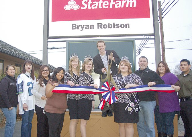 Sunnyside's newest State Farm insurance agent, Brian Robinson, prepares to cut the ribbon at his grand opening last Friday afternoon. On hand for the occasion at the 1503 E. Edison Ave. office were (L-R) Sunnyside Chamber of Commerce Executive Director Pam Turner, Dorris Kresse, State Farm employees Mallory Saldana and  Yesenia Godinez, Miss Sunnyside Princesses Leah Diddens and Ashley Davis, Miss Sunnyside Alyson Spidle, Sunnyside Mayor Jim Restucci, office manager Deana Lopez-Alanis and State Farm employee Roy Ramirez.