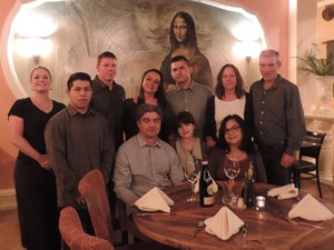 Romuls family gathering: Romul and Lillie Grivov, and their granddaughter, Bella, are flanked by Crystal Hager, left, Omar Lachino, Jerrett Bray, Jackie Bray, Pablo Moreno, Jill Monier and Steve Monier, with the image of the Mona Lisa, the dominant mural in the dining room.