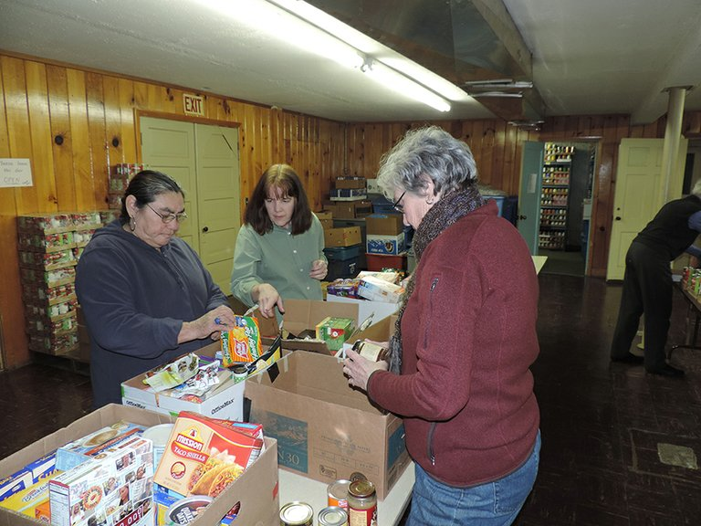 Volunteers Tonia Sanchez, left, and Cindy Allen, right, sort food at Hood River FISH, with help from site coordinator Lorinda Hoffman.