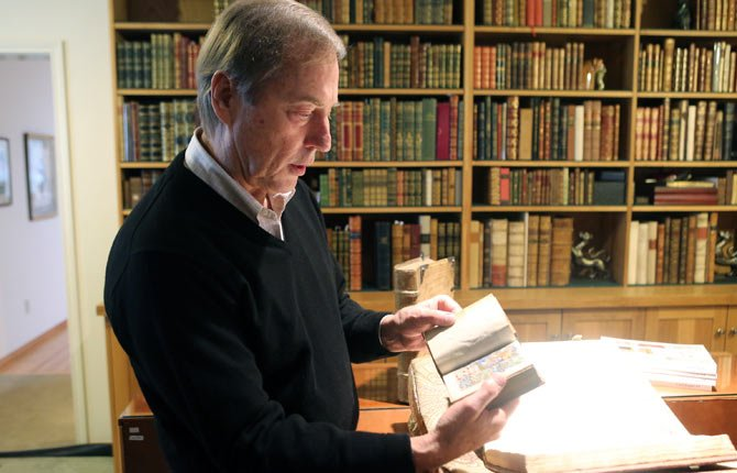 PHILLIP J. PIRAGES holds one of the items in his collection on antiquarian books, in McMinnville. Hidden in a rural area west of the city, Pirages has quietly built a reputation as one of the nation's foremost dealers of antiquarian books. His collection includes books and manuscripts more than a millennium old.