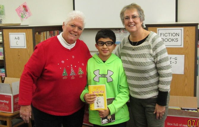 retired teachers and volunteers, Deanna Zaniker (left) and Beth Kaser (right) stand beside Chenowith Elementary School fifth grader Emilio Portillo just minutes after he made his selection from the free book offerings provided by Reading is Fundamental on Dec. 4.