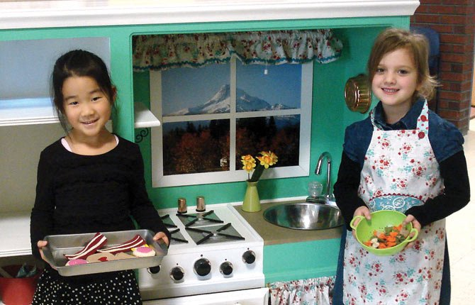 Ahyoung Kim, left and Sofia Rogers, right, kindergarteners at St. Mary's Academy, display some of the wares that are included with the decked out, custom-made kitchen that will be auctioned off Saturday, Feb. 1 at the 39th annual St. Mary's Super Auction. The kitchen, creatively repurposed from an entertainment center by St. Mary's parent Lori Nelson and her dad, Chuck Rosebraugh, is expected to spark a bidding war at the live auction.