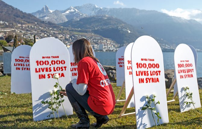 "A member of the Oxford Committee for Famine Relief, ""Oxfam"", puts a white rose on symbolic gravestones, on the opening day of the Geneva II peace talks on Syria, in Montreux, Switzerland, Jan. 22. Representatives of Syrian President Bashar Assad, a divided opposition, world powers and regional bodies started the peace conference."