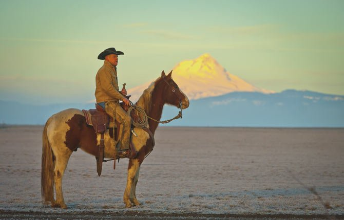 "MAUPIN RANCHER Keith Nantz and his horse ""Dude,"" top, enjoy a sunrise near his home before getting to work moving cows on a cold January day."