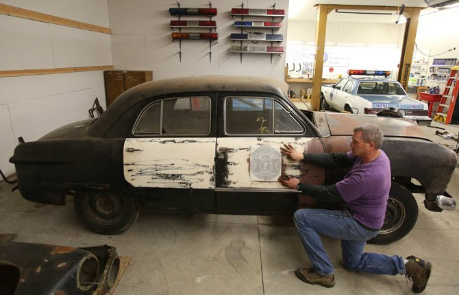Seattle police Officer Jim Ritter, of the Seattle Metropolitan Police Museum, holds an original side-door decal that is being used in the restoration project on a 1949 Washington State Patrol car. The restoration work is being done in Ellensburg, Wash.