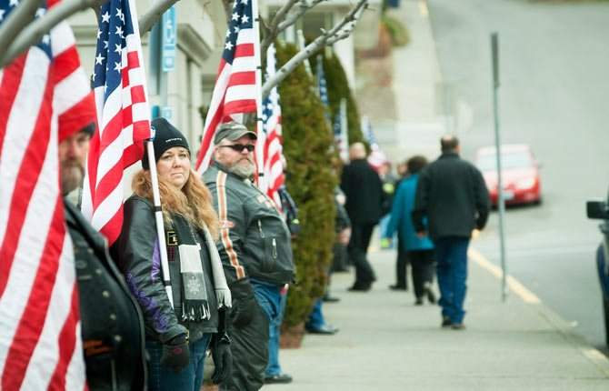 DAUN KING and Todd Klaviter of the Patriot Guard Riders, above, present flags along Fifth Street in front of the Wasco County Courthouse Jan. 25 as guests arrive for a celebration and remembrance of the life of Tim Lynn, Wasco County Assessor, who died Jan. 16, 2014, and was a Coast Guard veteran.