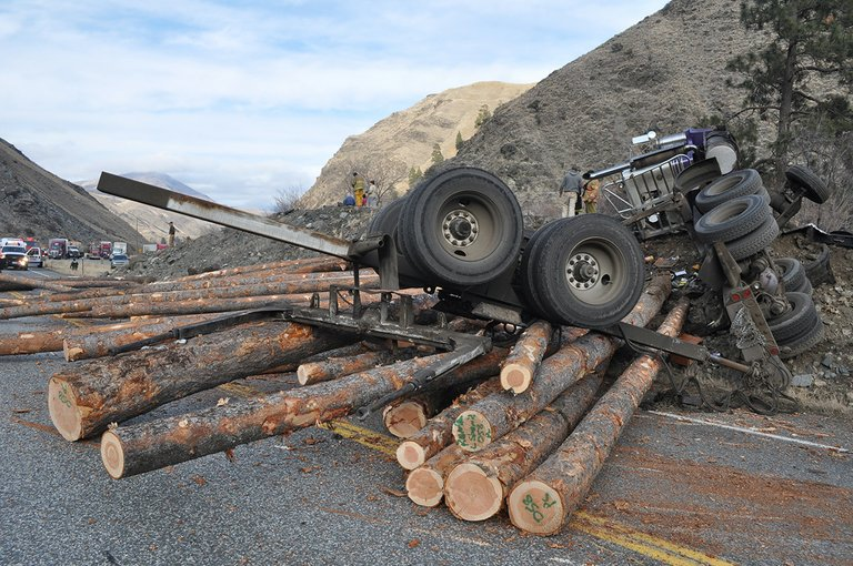 An overturned log trailer sits atop a pile of logs spilled across U.S. Highway 95 at the north entrance to Pollock Monday afternoon, Jan. 27, following a semi-truck rollover. The driver, Michael J. Clure of Horseshoe Bend, was transported to McCall for treatment.