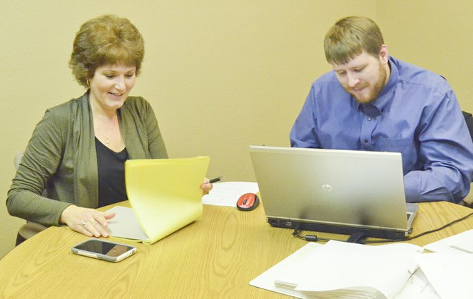 Sunnyside Valley Irrigation District Assistant Manager of Administration Lori Brady confers with Brian Bender of The Resource Group regarding software changes recently made at the irrigation district.