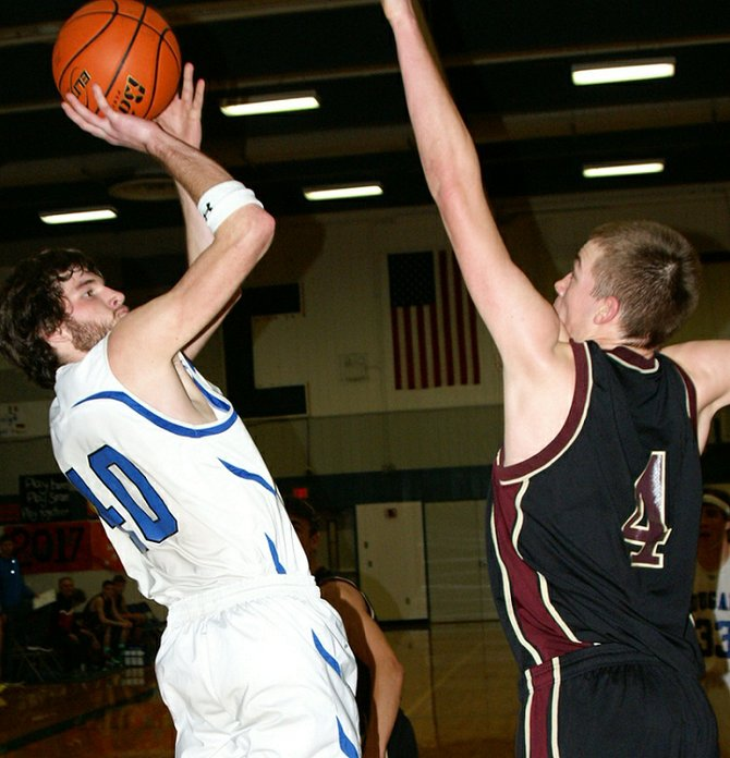 Lyle/Wishram's Jonathan VonAhn puts up a baseline jumper over Sunnyside Christian's        6-foot-7 Darren Broersma last Saturday. Lyle/Wishram lost the Greater Columbia 1B League contest, 50-39, after leading 21-20 at halftime. VonAhn led the Cougars with 16 points.