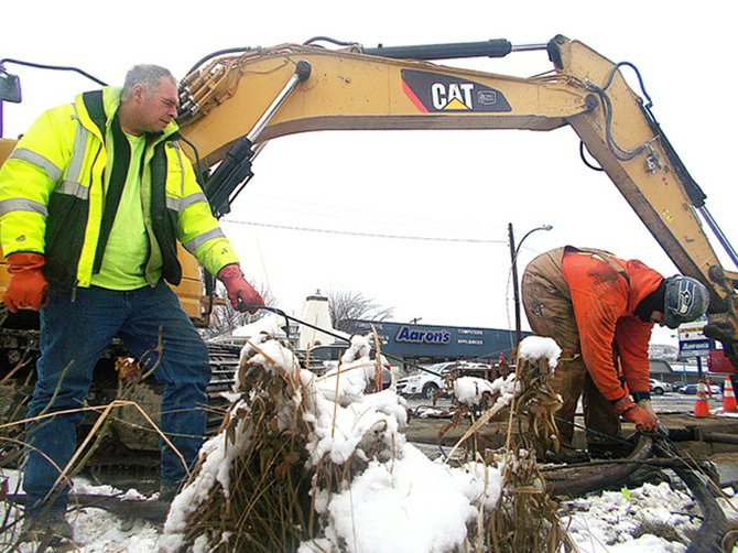 Despite overnight snowfall, Buno Construction's Brian Maddox of Lake Stevens, left, and Jake Grant of Snohomish continue upgrade work on the city sewer system Wednesday morning in Omak.