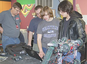 The Sunnyside High School robotics teams are continuing to succeed at local competitions. From left, advisor Spencer Martin helps Ethan Partch, Cody Woodworth and Sebastian Castellanos w