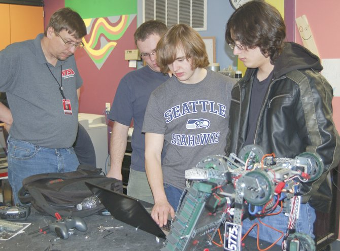 The Sunnyside High School robotics teams are continuing to succeed at local competitions. From left, advisor Spencer Martin helps Ethan Partch, Cody Woodworth and Sebastian Castellanos work on a software issue with their robot, 5775c, that recently took top honors out of 40 teams from 15 local schools at a competition at East Valley High School. All four SHS robotics teams are qualified for the state VEX competition, which will be held Sunday, Feb. 16, in Toppenish.
