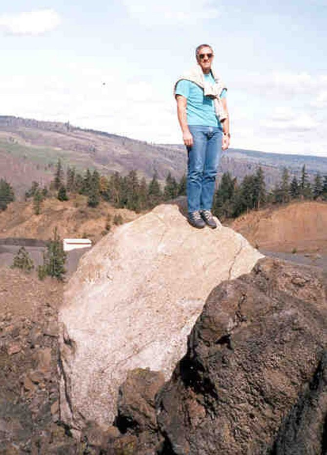 Geologist Mac Jervey stands on the Mosier Erratic, a 6'x8'x12' quartz boulder at the Twin Tunnels trailhead west of Mosier. 	Contributed photo