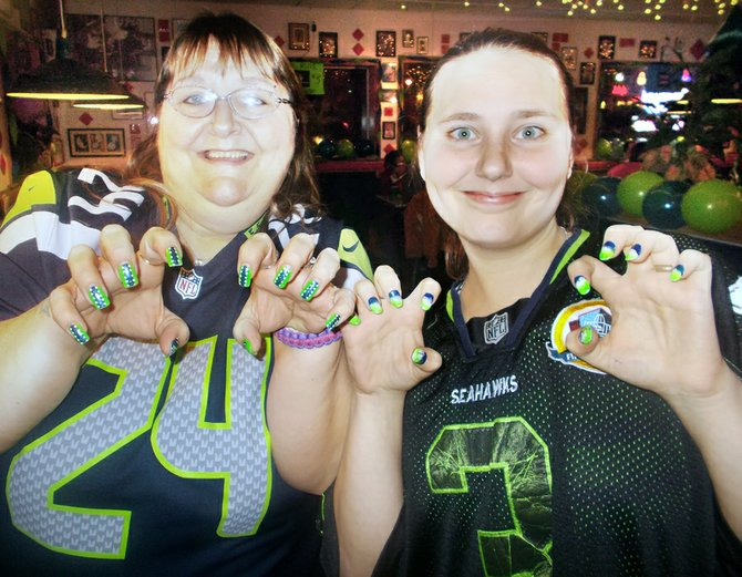 Kim and Sierra Fain, both of Omak, show off their themed fingernails Wednesday night during the Seahawk Rally at Hometown Pizza.