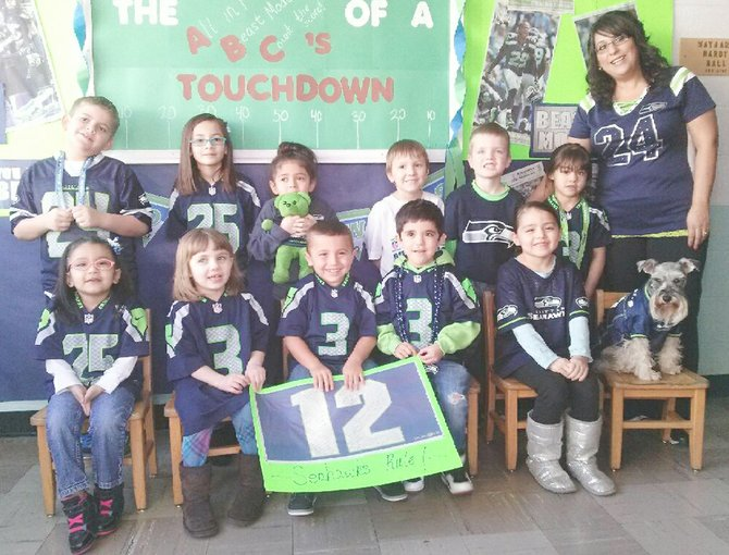 Audrey Brandsma's students at Sunnyside's United Methodist Pre-School, like the rest of the community, are in 12th Man mode for this coming Sunday's Super Bowl game that pits the Seattle Seahawks against the Denver Broncos. Joining the local teacher and her students for the photo shoot was the class mascot, Faith.