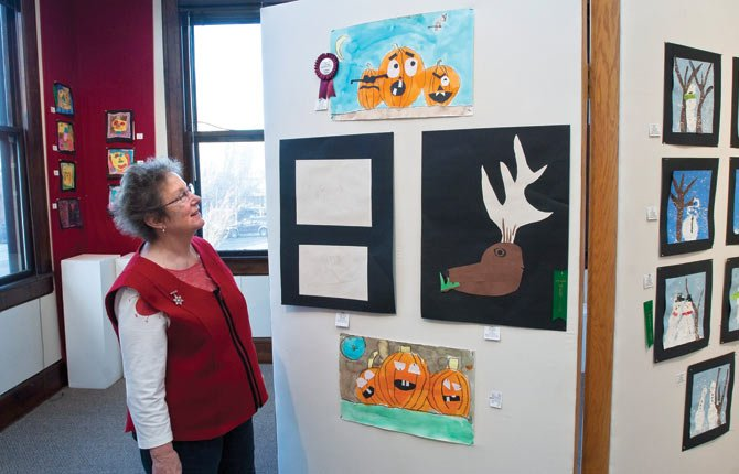 The Dalles Art Center volunteer Ann Marie Woolsey admires some of the many entries in the elementary art exhibit, including the judges choice, at top left. A reception and award presentation is set for Saturday, Feb. 1, from 3 to 4 p.m. Exhibitors will take home their work at that time.