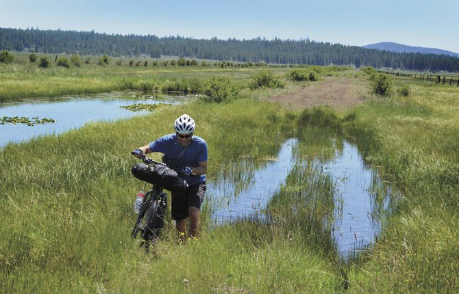 In this June 7, 2013 photo, Donnie Kolb pushes his bike through a marshy section of Sycan Marsh near Klamath Falls, Ore.  Kolb has been organizing gravel bicycle rides for the past five years, usually keeping his events a bit on the down low.  His outings are unsupported, unsanctioned, have no entry fee and crown no winner.