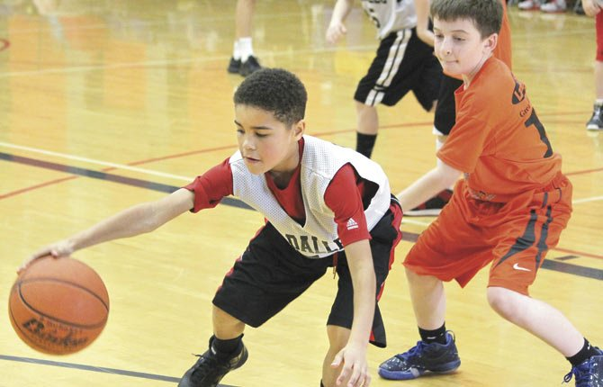 THE DALLES youth hoops player Styles DeLeon (left) hustles to the sidelines for a loos ball while being closely defended by a Sherman County player in tournament action last weekend. The Columbia Gorge Basketball Academy currently has 50 youth boys participating on Travel Basketball Teams this winter.