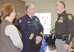 Retiring Police Chief Dave Charvet and his wife, Kelley, visit with Sheriff Ken Irwin (right) at last Friday's retirement party held in Charvet's hono