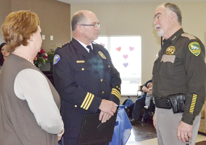 Retiring Police Chief Dave Charvet and his wife, Kelley, visit with Sheriff Ken Irwin (right) at last Friday's retirement party held in Charvet's honor.