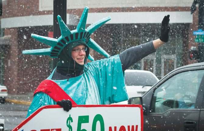 DRESSED as the Statue of Liberty, Austin Black works undaunted through a heavy fall of snow Monday afternoon on Third Street, downtown The Dalles, where he is trying to gain attention for a local tax firm.