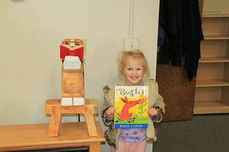 "Catherine Seubert, age 4, is shown with the mascot at Prairie Community Library. She won the ""name the dog contest"" and called him Buster."