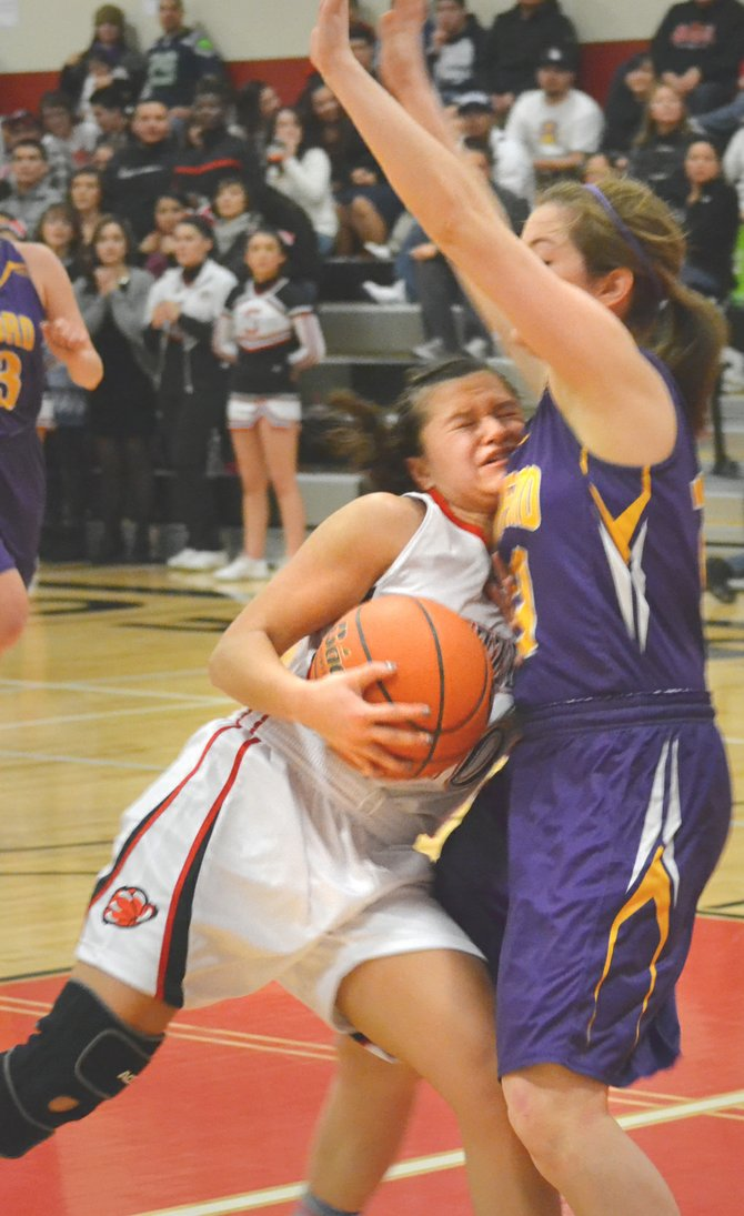 Sunnyside's Selena Rubalcava tries crashing her way into the paint, only to be denied by Hanford's Ashley Stewart.
