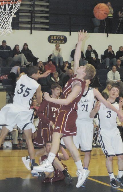 TDW'S Devin Wilson (middle) fires in for a rebound in Tuesday's hoops game. Wilson and Tribe had a 25-7 second-half run in a 52-35 win.