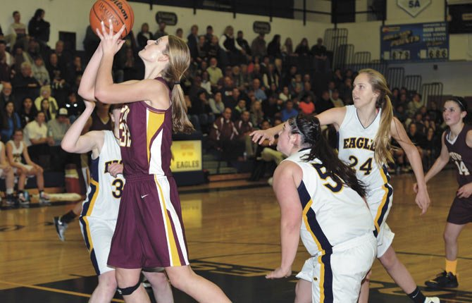 THE DALLES WAHTONKA center Olivia Starks (front) leans in for a shot while Hood River Valley's Mykan Malon (30), Marlie Bloomster (24) and Annie Veatch (55) defend in the first half of Tuesday's Columbia River Conference hoops game in Hood River. Starks scored 10 points and had seven boards and six blocks to lead the No. 4-ranked Tribe to a lopsided 54-21 triumph over the Eagles.