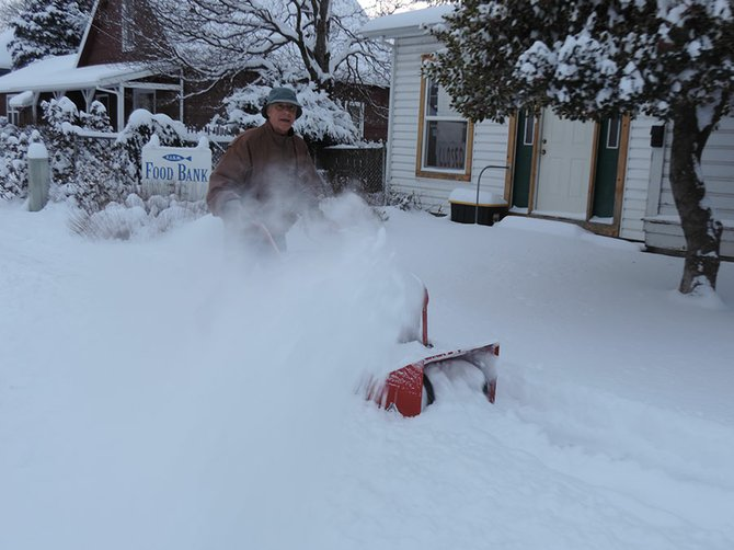 Kevin Hay, a Pine Street resident and co-owner of nearby E & L Auto Parts, uses his snowblower to clear the block on the Heights Friday morning.