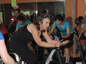 Kristie Cater uses humor to encourage riders in her cycling class at the Sports Club.