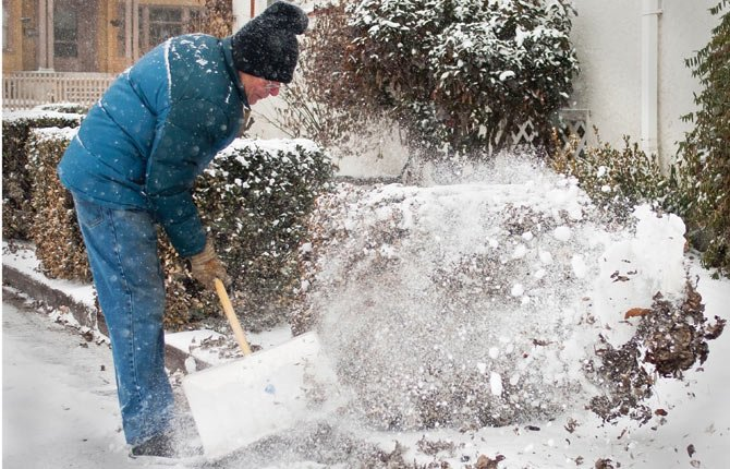 """Ron Engman shovels the walkway outside a local insurance agency in The Dalles. """"It's to say 'Thank you,' he said. """"I brought a friend in here and they took really good care of her."""" Others in need of snow removal can also get the handymans shovel services for an hourly fee."""