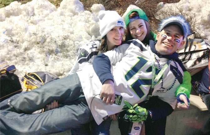 LIFELONG Seattle Seahawks fan Dennis Everts, a native of The Dalles, lays perpendicular to his wife Tami (left rear) and Taylor while the trio recently visited East Rutherford, New Jersey for Super Bowl XLVIII. Since purchasing season tickets in 1993, Everts has used sports to provide a strong family bond.