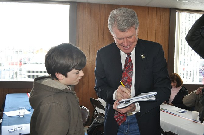 """Idaho Governor C.L. """"Butch""""Otter brought state governmental officials to Craigmont last Friday, Feb. 7, for the monthly Capitol for a Day event. Here he signs a note of appreciation for attending the event to (left) Aidan Acton, 10, of Grangeville."""
