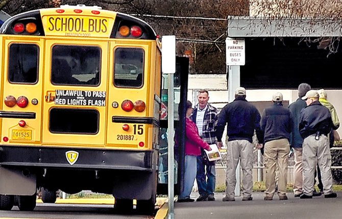 A row of private security guards lines an apparent replacement teacher as she gets off the bus at Medford's Central High School gym Feb. 10 in Medford. Police said about 150 pickets greeted the substitutes as buses hauled them from their motels to Central Medford High School for a review of their credentials and for drug screening.